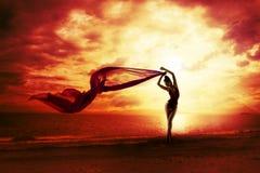 Silhouette sexy de femme au-dessus de ciel rouge de coucher du soleil, plage femelle sensuelle Images stock