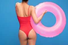 Silhouette of fit woman in red swimsuit. Silhouette of fit woman in red swimsuit holding inflatable pink circle, posing on blue background. Back view stock photo