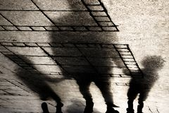 Silhouette shadow of a father holding hands with two small boys royalty free stock image