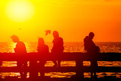 Silhouette shadow group of teen friendship at sea coast. In sunny dusk summer hot day Royalty Free Stock Photo