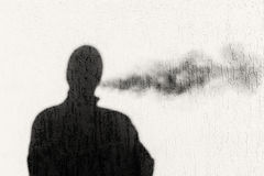 Silhouette Shadow of a Man Exhaling Smoke Stock Photo