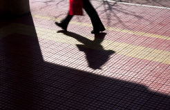 Silhouette and shadow of a person on a city sidewalk. Blurry silhouette and shadow of a person walking and carrying a red bag  on a city sidewalk , from waist Stock Image