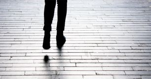 Silhouette shadow of person legs walking. Away on paterned walkway in black and white Royalty Free Stock Image
