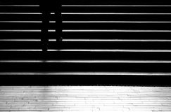 Silhouette shadow of a person walking up the city stairs. Silhouette shadow of person legs walking up the public stairs in subway passage on the night in black Royalty Free Stock Photography