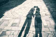 Silhouette shadow of two people holding hands and kissing Stock Photo
