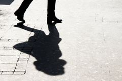 Silhouette shadow of woman walking. Silhouette shadow of woman legs walking city street in black and white royalty free stock image