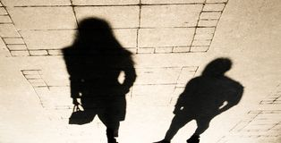 Silhouette shadow of a woman and a man on city sidewalk. In sepia black and white royalty free stock photography