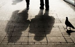 Silhouette shadow of a woman , a man and a pigeon on city sidewalk. In sepia black and white royalty free stock photo