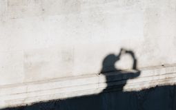 Silhouette shadow of young woman in a old wall taking photo at the sky in a sunny day royalty free stock images