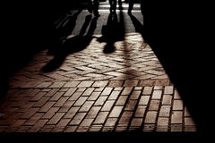 Silhouette shadows, People Walking. Silhouetted shadows of people walking on brick pavement, strongly backlit, stylized Stock Photography