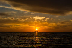 A silhouette of a ship on the horizon. A silhouette of a ship on the horizon, a setting sun and colored orange and yellow clouds at the beach of Black sea Royalty Free Stock Photos
