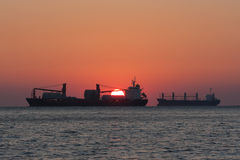 Silhouette of a ship leaving for sailing. On a sunset background royalty free stock photo