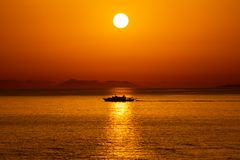 Silhouette of a ship passing in the reflection of the Sun in the Ionian Sea, Sarande, Albania. stock image