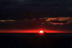 Silhouette of ship at sunset in the ocean Stock Images