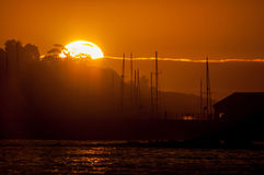 Silhouette of ships masts against sunset over a harbor Royalty Free Stock Photo