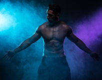 Silhouette Shirtless Muscled Man Posing in Smoke Stock Image