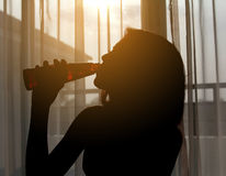 Silhouette shot of a female drinking red wine. In a  room Stock Image