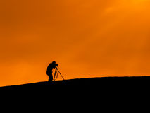 Silhouette shot of a photographer taking a photo. Over the hill Stock Image