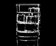 Silhouette of simple glass with ice cubes in the low-key lighting. And surface reflection. Toned royalty free stock images