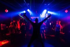 Silhouette of the singer at a live concert at the club at the event against the crowd. Of people in the audience royalty free stock image
