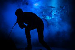 Singer at the concert. Silhouette of a singer with a microphone at a concert on the background of drums in smoke with blue lighting stock photo