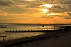 Silhouette of a single boat at sunset on a low tide stock image