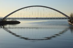 Silhouette of a single mounted cyclist on Humber Bay Arch Bridge. The silhouette of a single mounted cyclist contributes to the symmetrical shadowing of the Stock Images