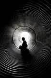 The silhouette of the sitting boy. With light at the end of the tunnel Royalty Free Stock Image