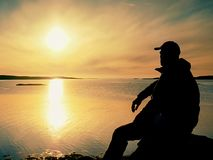 Silhouette of sitting man on stony coastline. Hiker seeing over bay to evening sun. Silhouette of sitting man on stony coastline. Hiker seeing over siklent bay Royalty Free Stock Image