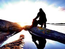 Silhouette of sitting man on stony coastline. Hiker seeing over bay to evening sun. Silhouette of sitting man on stony coastline. Hiker seeing over siklent bay Stock Image