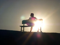 Silhouette sitting in sunset. Silhouette of a man sitting in sunset Royalty Free Stock Photo