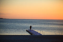 Silhouette sitting young woman on sunset Royalty Free Stock Photos
