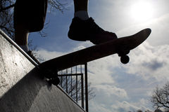 Silhouette of a skateboarder on a half pipe Stock Image
