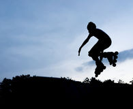 Silhouette of a skater in a jump against the blue sky stock photography