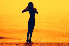 Silhouette of a skinny young girl walking along the beach. Silhouette of a slim young girl walking along the beach, pink tone stock images