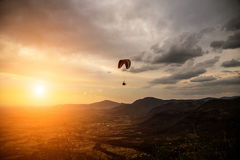 Silhouette of sky diver flies on background of sunset sky. People fly a paraglider on a background of beautiful scenery Royalty Free Stock Photo