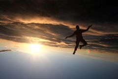 Silhouette of a skydiver. Flying head down in sunset Royalty Free Stock Photos