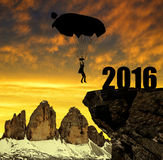 Silhouette skydiver parachutist landing in to the New Year 2016. At sunset Royalty Free Stock Images
