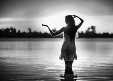 Silhouette of the slender girl in an easy dress in the lake at sunset Stock Images