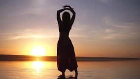 Silhouette of a slender girl walking on the water in yoga pants, raises her hands. Carefree, freedom. Incredible sunset