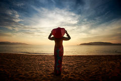 Silhouette of slim girl in long and hat in sunrise over sea Stock Photography