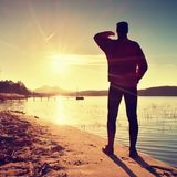 Silhouette of slim person ondecline seeing off sun. Mn with hand in the air Royalty Free Stock Images