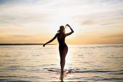 Silhouette of slim sexy woman in bikini walking on the beach. At sunset Stock Photo
