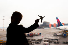 Silhouette of a small airplane model on airport in kids hands. Black Silhouette of a small airplane model on airport in kids hands royalty free stock photos