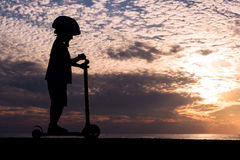 Silhouette of small boy wearing helmet on scooter on background of ocean sunset Royalty Free Stock Photos
