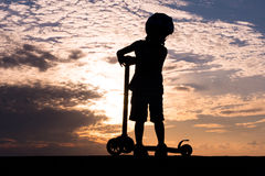 Silhouette of small boy wearing helmet with scooter on background of sea sunset Stock Image