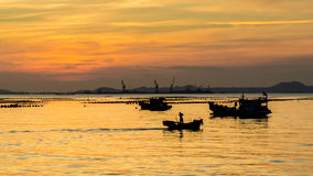 Silhouette of small fisherman boat in sea with sunset sky Stock Photos