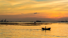 Silhouette of small fisherman boat in sea with sunset sky Royalty Free Stock Image