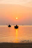 Silhouette of Small fishing boats on the sea during sunrise Royalty Free Stock Images