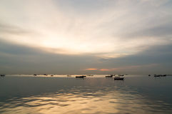 Silhouette of Small fishing boats on the sea during sunset Royalty Free Stock Image